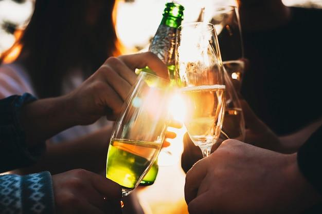 Ritaglia le mani dei giovani che tintinnano bicchieri e bottiglia di alcol contro il sole splendente mentre celebravano insieme le vacanze in campagna