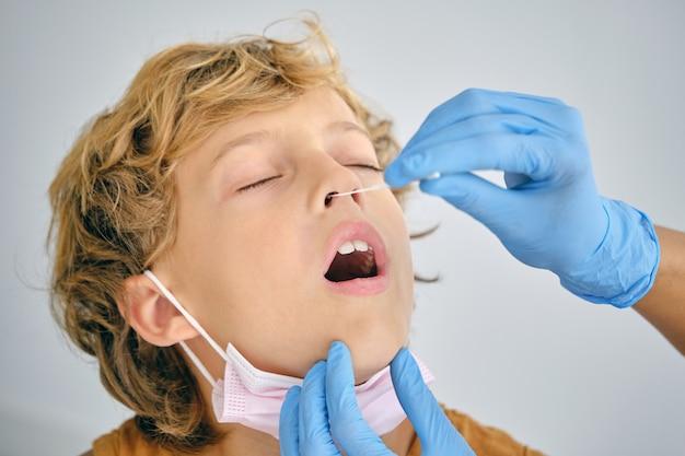 Medico delle colture che esegue il test del coronavirus da un ragazzo in ospedale