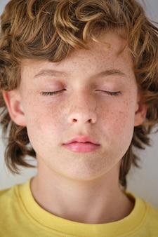 Ritaglia un ragazzo attento con le lentiggini sulla pelle del viso