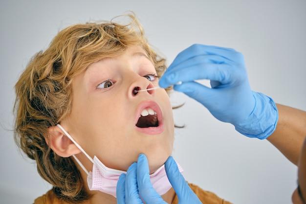 Infermiera del raccolto che fa il test del coronavirus da un ragazzo impaurito in ospedale