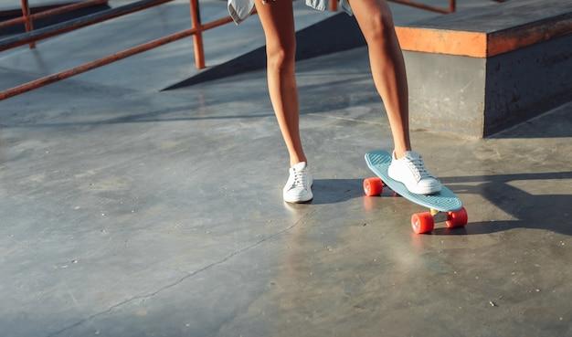 Ritaglia la foto della pattinatrice con la tavola da crociera allo skatepark