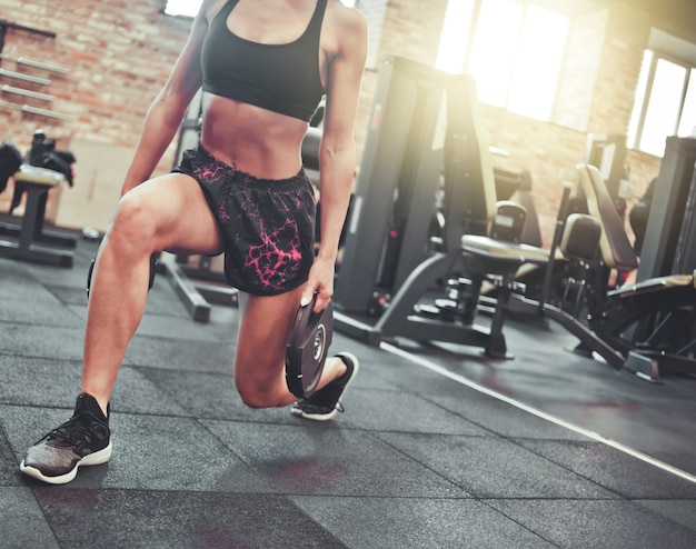 Ritaglia la foto bruna sportiva sottile facendo esercizi di affondi con le gambe con bilanciere nelle mani della palestra.