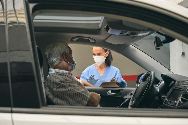 Ritaglia il medico che parla con il conducente anziano in auto durante il check-up in auto