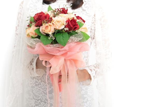 La maschera del raccolto del fiore d'uso della tenuta del vestito da sposa dalla bella donna asiatica