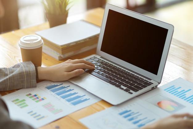 Colpo di raccolto di giovane bella donna d'affari concentrata che lavora su laptop e documenti di dati finanziari in un ufficio moderno e luminoso