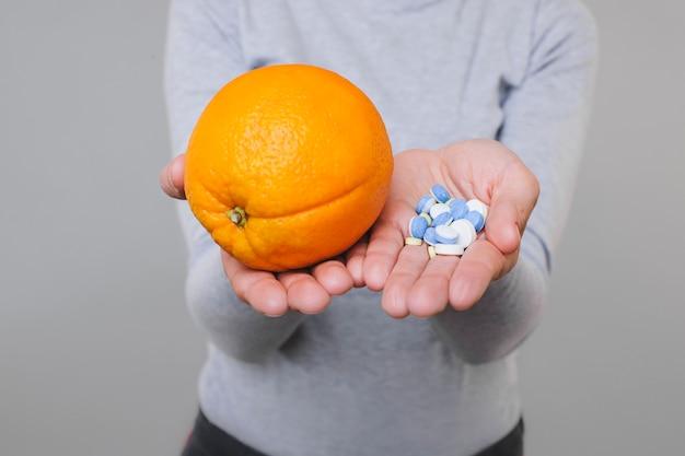 Ritaglia la donna in camicetta che mostra arancia fresca e mucchio di medicamento sulle palme su grigio