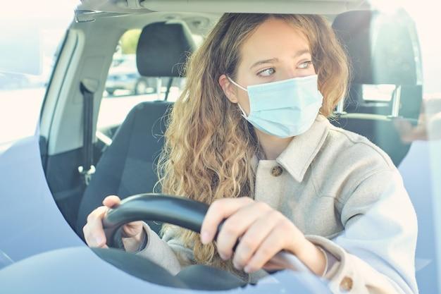 Ritaglia la donna con la maschera facciale alla guida di un'auto moderna in città