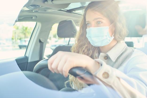 Ritaglia la donna in maschera medica alla guida di un'auto contemporanea in città