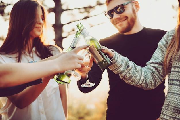 Ritaglia i giovani che tintinnano bottiglie di birra e bicchieri di champagne mentre festeggiano in una giornata di sole nella natura