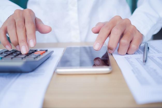 Donna di mano ritagliata utilizzando la calcolatrice con mobile sul tavolo di legno. concetto di affari.