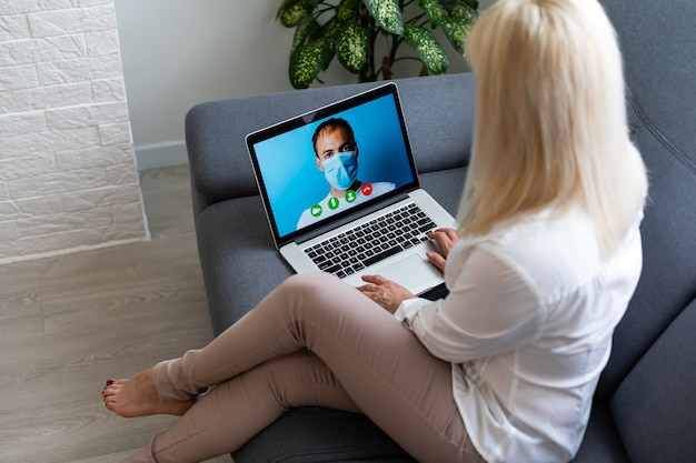 Vista posteriore ritagliata della giovane donna in una stanza luminosa e luminosa all'interno di un accogliente appartamento utilizzando un computer portatile. lei parla con un buon dottore attraverso internet