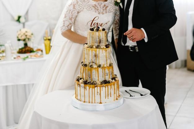 Una sposa e uno sposo ritagliate stanno tagliando la loro torta nuziale rustica
