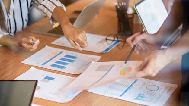 Ritagliata di donna d'affari che punta il dito sulle scartoffie nella sala riunioni meeting