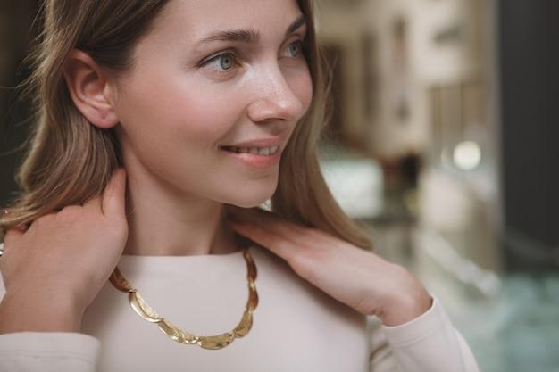 Ritagliata da vicino della donna allegra sorridente, indossa una collana d'oro