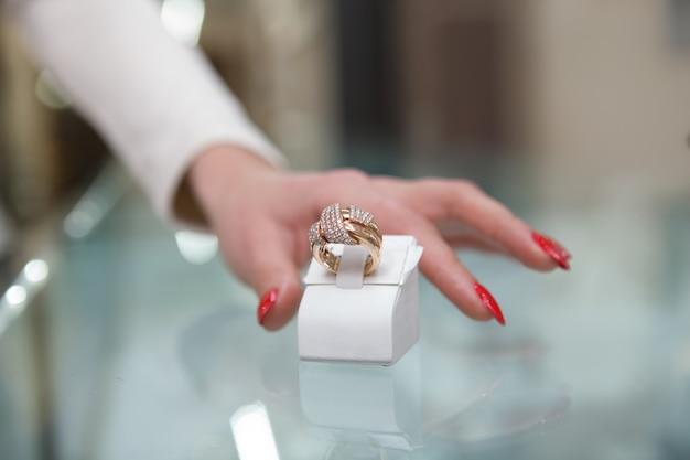 Ritagliata stretta di mano femminile protesa per anello di diamanti dorati
