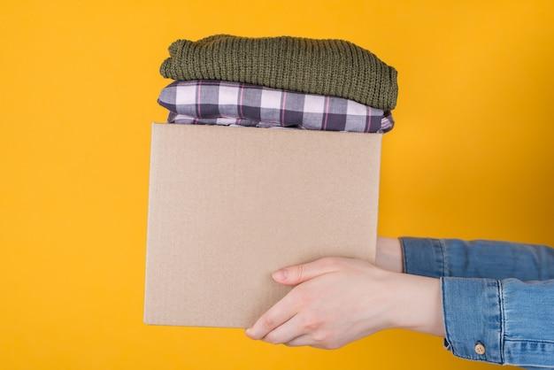 Foto ravvicinata ritagliata della scatola delle donazioni di vestiti isolata su sfondo giallo