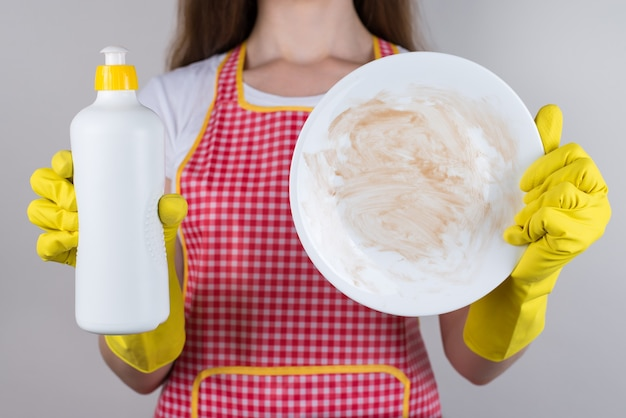 Foto ravvicinata ritagliata di una madre triste sconvolta e infelice che usa un detergente chimico ma sogna di una nuova lavastoviglie isolato sfondo grigio