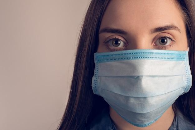 Ritagliata da vicino la foto della ragazza sconvolta che indossa la maschera medica blu che guarda l'obbiettivo isolato sopra il muro grigio con lo spazio della copia