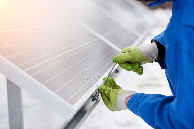 Potato vicino su di un riparatore che ripara il modulo blu del pannello solare all'aperto