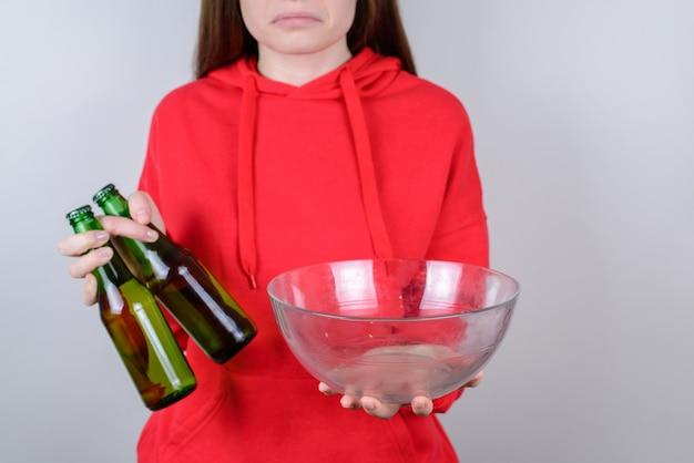 Primo piano ritagliato di una persona che fa smorfie confusa e delusa che tiene in mano uno sfondo grigio isolato su un piatto vuoto