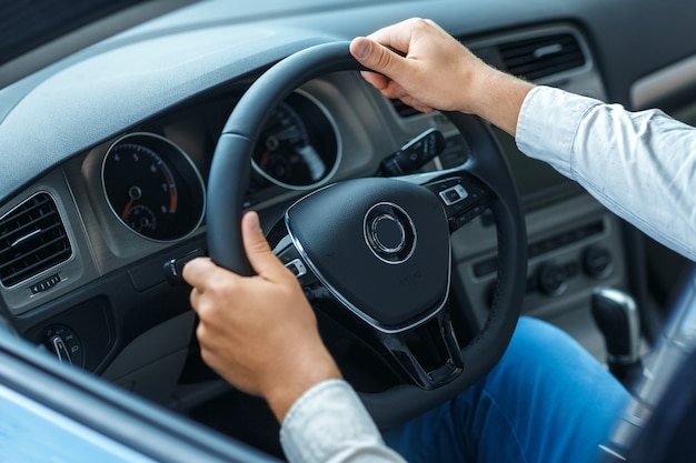 Colpo del primo piano potato delle mani di un uomo su un volante