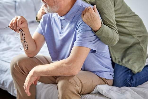 Ritagliata coppia di anziani seduti sul letto trascorrere il tempo libero nei fine settimana, donna che abbraccia l'uomo dalla parte posteriore. a casa in abbigliamento casual