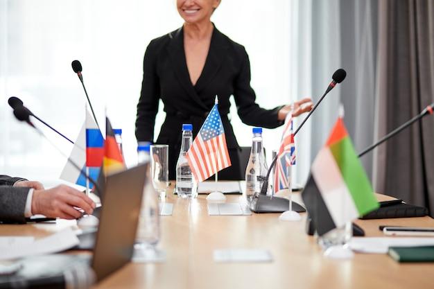 Dirigente femminile ritagliata in abito formale che tiene discorsi con leader politici di altri paesi, persone diverse riunite in conferenza stampa, riunioni senza legami. concentrarsi sulla bandiera da tavolo
