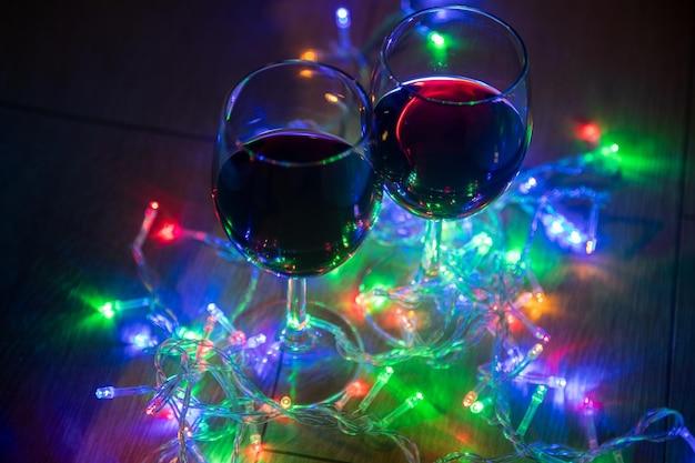 Mano ritagliata che tiene il bicchiere di vino su luci di natale illuminate colorate in camera oscura