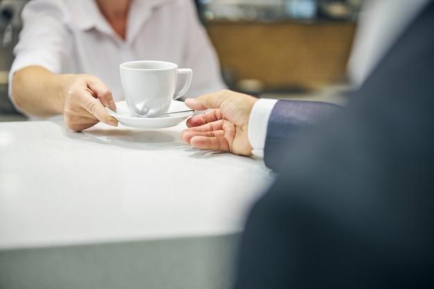 Testa tagliata ravvicinata delle mani della cameriera che dà l'ordine di una tazza di tè all'uomo in abito