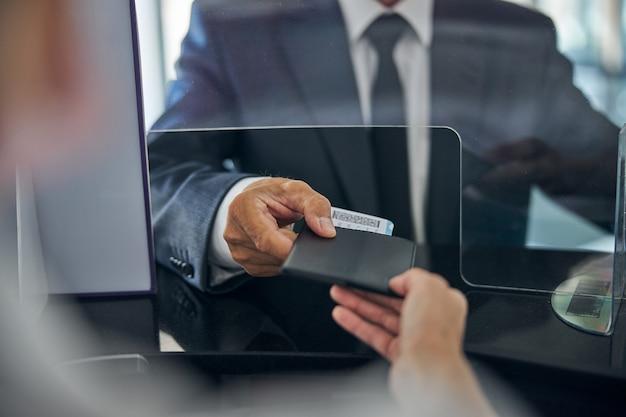 Testa ritagliata primo piano delle mani maschili e femminili con passaporto e carta d'imbarco durante la registrazione
