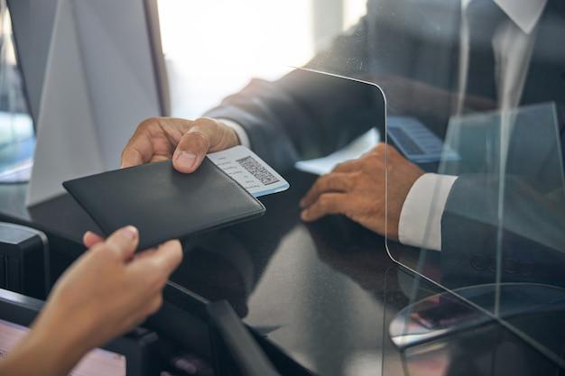 Testa ritagliata primo piano dell'uomo in tuta con passaporto e carta d'imbarco mentre dà al manager all'aeroporto