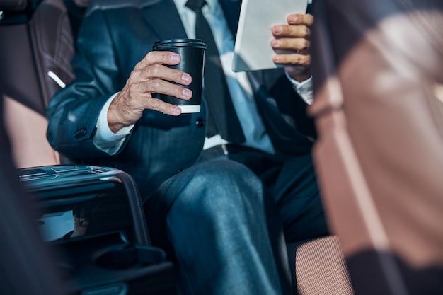 Testa tagliata di un uomo elegante in giacca e cravatta seduto dietro con una tazza di bevanda calda e touchpad durante il trasferimento