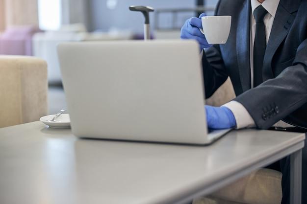 Testa tagliata di uomo in tuta e guanti in lattice usando il taccuino e bevendo caffè prima del volo