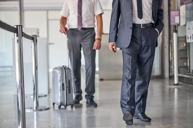 Testa tagliata di uomo in abito elegante e cravatta che cammina con l'assistente che trasporta i bagagli in aeroporto
