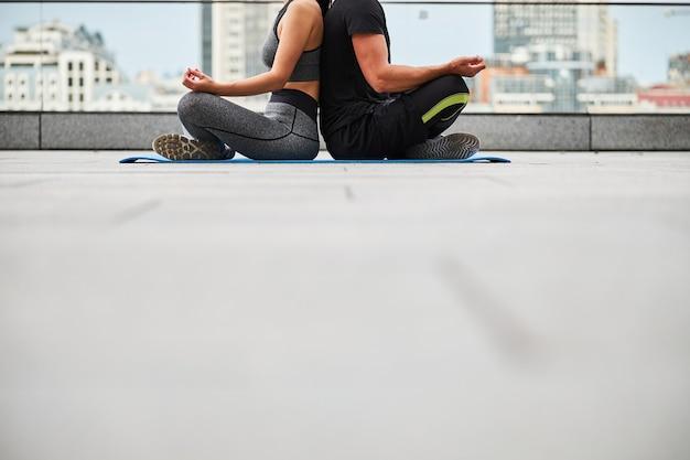 Testa tagliata di uomo e donna in abito seduto nella posizione del loto schiena contro schiena sulla terrazza dell'edificio urbano