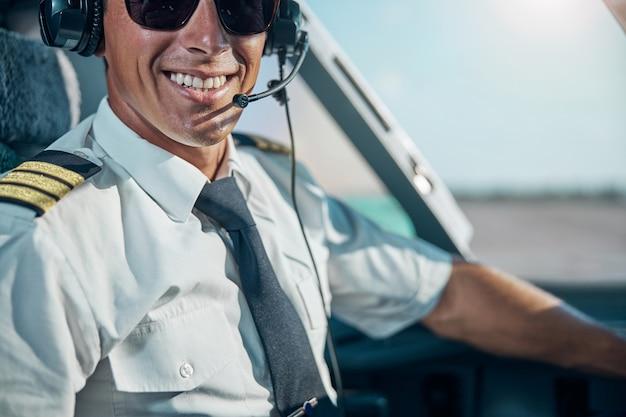 Ritratto di testa tagliata di un bell'uomo allegro con cuffie professionali seduto al controllo in cabina di pilotaggio
