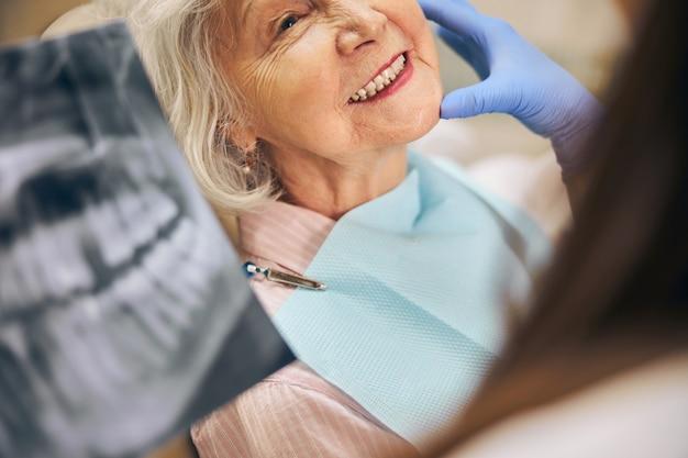 Testa ritagliata ritratto di donna anziana che mostra i suoi denti al dentista femminile mentre si consulta con uno specialista professionista