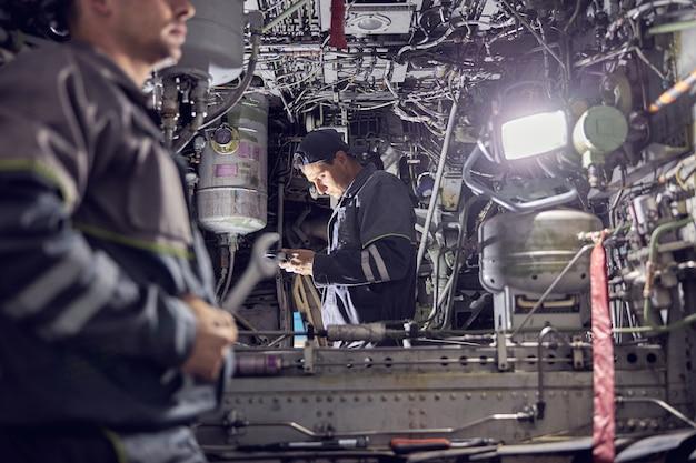 Il ritratto della testa ritagliata del meccanico e dell'ingegnere che indossano l'uniforme stanno lavorando all'interno dell'aereo con strumenti per l'aviazione e altre attrezzature