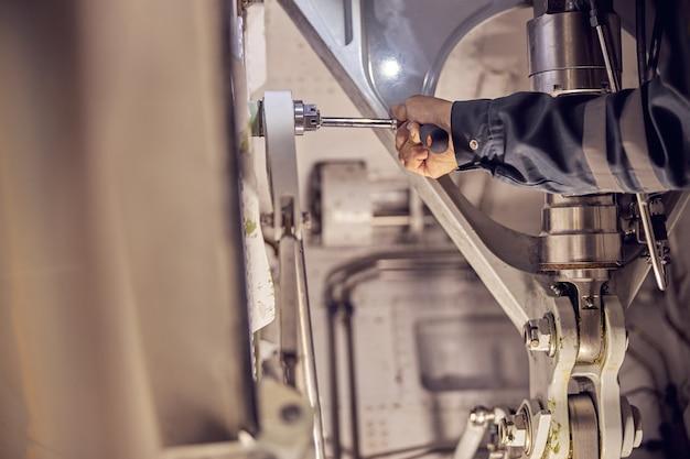 Ritratto della testa ritagliata della mano del meccanico che utilizza strumenti speciali per il fissaggio e il controllo del sistema di aerei passeggeri nell'hangar dell'aviazione