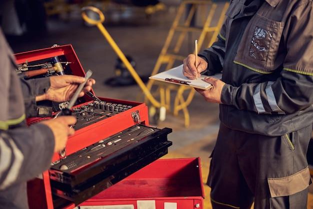 Ritratto di testa tagliata di uomini aerei con strumenti in mano e un altro maschio che fa appunti negli appunti