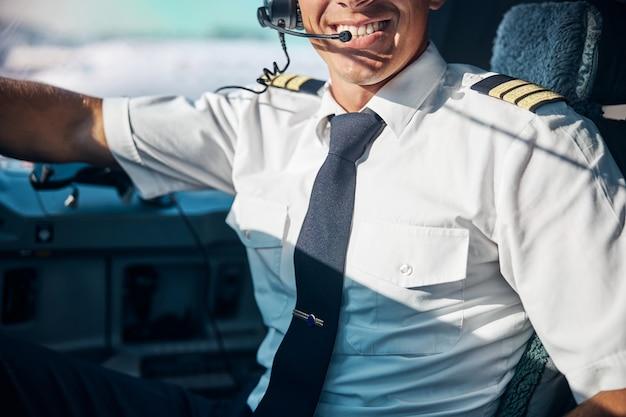 Ritratto di testa tagliata di un bell'uomo sorridente seduto nella cabina di pilotaggio con auricolari professionali pronti a decollare