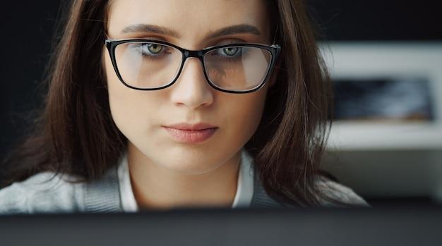 Headshot ritagliata della giovane donna concentrata che lavora al computer, riflesso della digitazione delle mani in occhiali