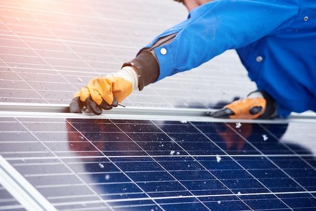 Colpo orizzontale potato di un lavoratore maschio che installa i pannelli solari su una centrale elettrica