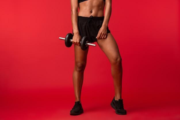 Immagine ritagliata della donna afro-americana in abiti sportivi neri sollevamento manubri, isolato sopra la parete rossa