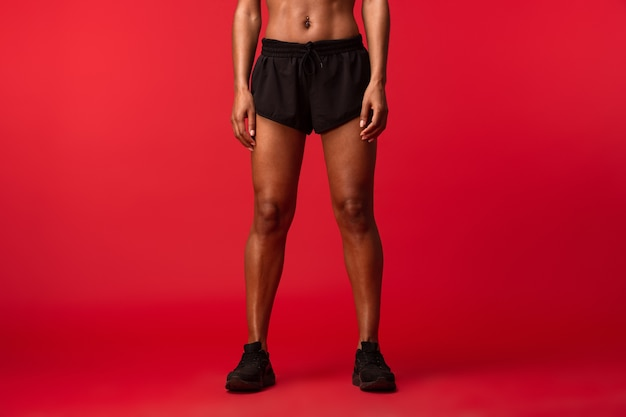 Immagine potata della donna afroamericana in abiti sportivi neri in piedi, isolata sopra la parete rossa