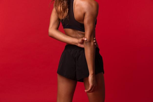 Immagine potata della donna afroamericana in abiti sportivi neri che allunga il suo corpo, isolato sopra la parete rossa