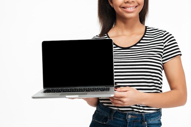 Immagine potata di una donna africana che presenta il computer portatile dello schermo in bianco