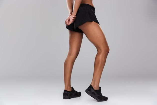 Immagine ritagliata di incredibile bella donna sportiva forte in posa isolata.