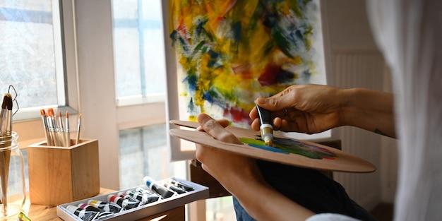 Immagine potata delle mani dell'artista mentre tenendo e mescolando colore a olio sulla tavolozza dell'artista sopra la pittura