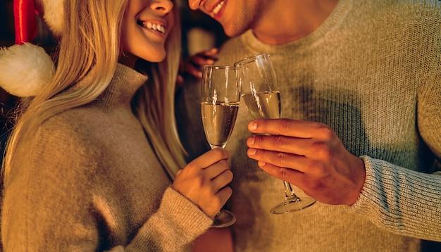 L'immagine ritagliata di bella giovane coppia in cappelli di babbo natale è in possesso di bicchieri di champagne e sorridente mentre celebrava il nuovo anno a casa.